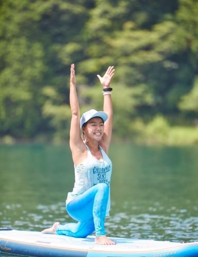 湖の上で笑顔でヨガをする田中律子